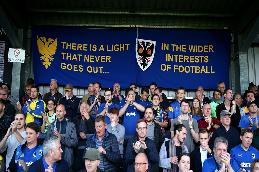 """Photograph of football fans at Wimbledon football club with a banner reading """"there is a light that never goes out...in the wider interests of football"""""""