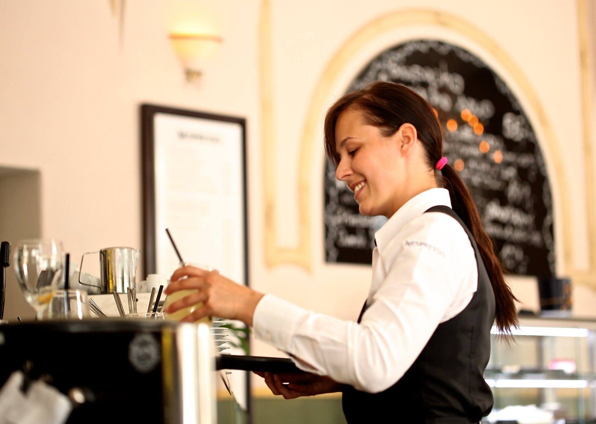 Waitress carrying a tray with cocktail on