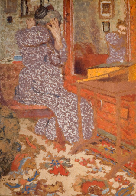 Oil on cardboard painting of Madame Vuillard (Édouard Vuillard's mother) arranging her hair in a mirror. The figure is turned away from the viewer and her face is not shown. The painting in largely orange toned, with Madame Vuillard contrasting this in her purple dress with a white curved line pattern. She is situated mainly in the top-left corner of the painting. The carpet on the floor is largely beige and red and appears to be oriental in style. The carpet takes up most of the lower-third of the image. The mirror Madame Vuillard is sat in front is part of a large, orange wood cabinet. It takes up the upper-right corner of the frame.