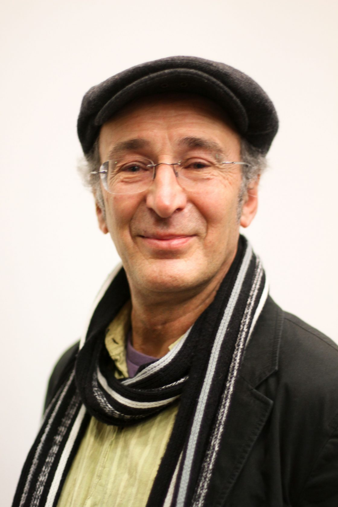 Photograph of Mike Layward who is the artistic director of DASH. He is facing the camera, wearing a black flat cap and long striped scarf.