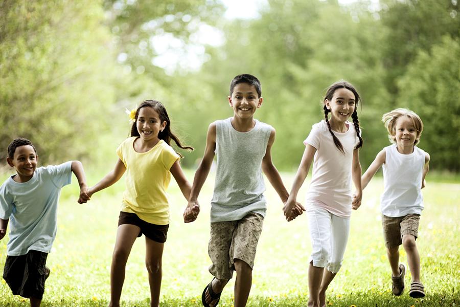 Children running in a line holding hands.