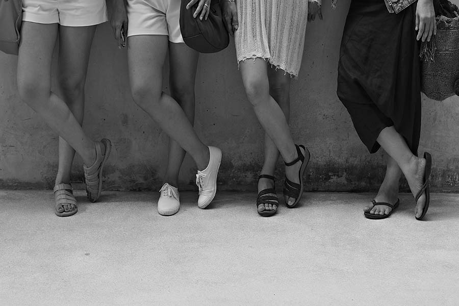 Women standing with cross legs in same position. Black and white picture of women's legs.