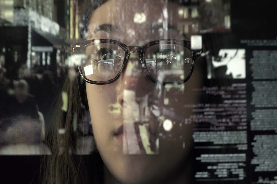 An woman concentrating on a touch screen display. The point of view is from behind the screen, looking through the data & images to the woman's face and hands as she manipulates the windows of information.