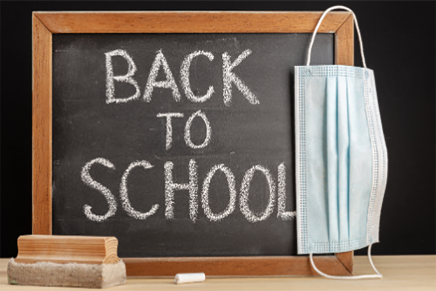 A blackboard reading back to school with a face mask hanging over