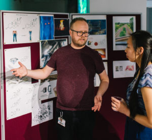 A photograph of IMSR researcher Jonathan Mueller talking to members of the public about his research on sulfation pathways and steroids at an engagement event