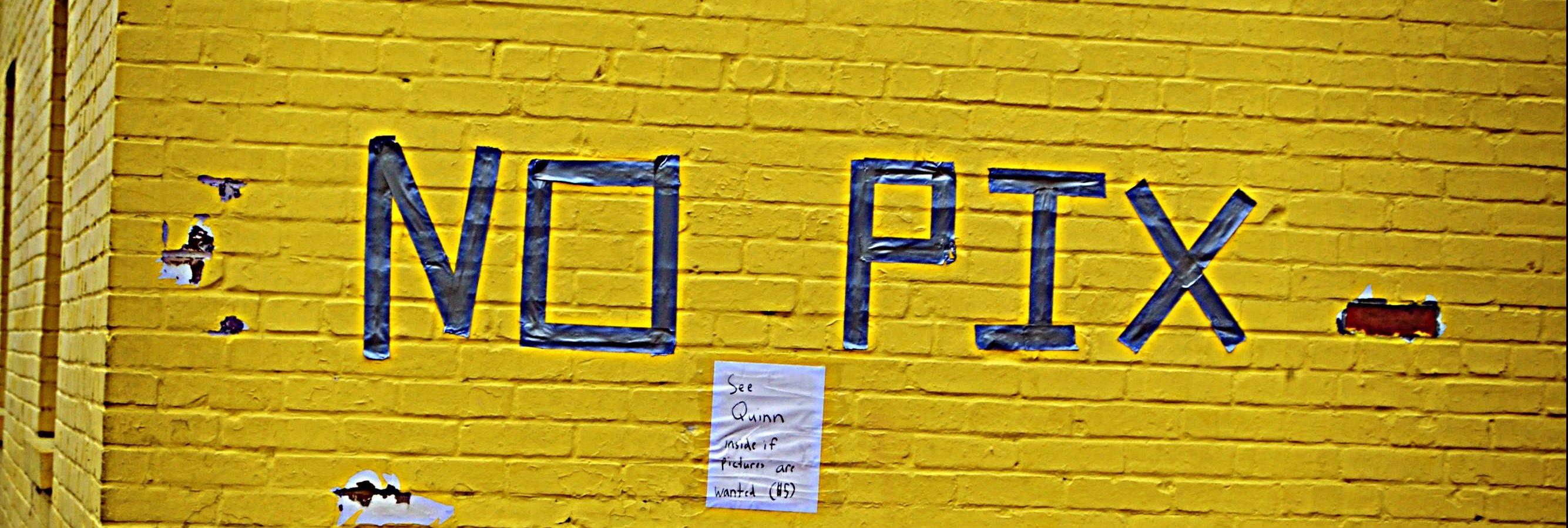 """""""No Pix"""" grafiti art on a yellow brick wall"""